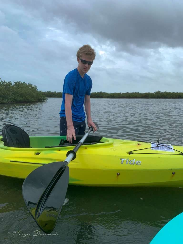 boy standing in water next to kayak.