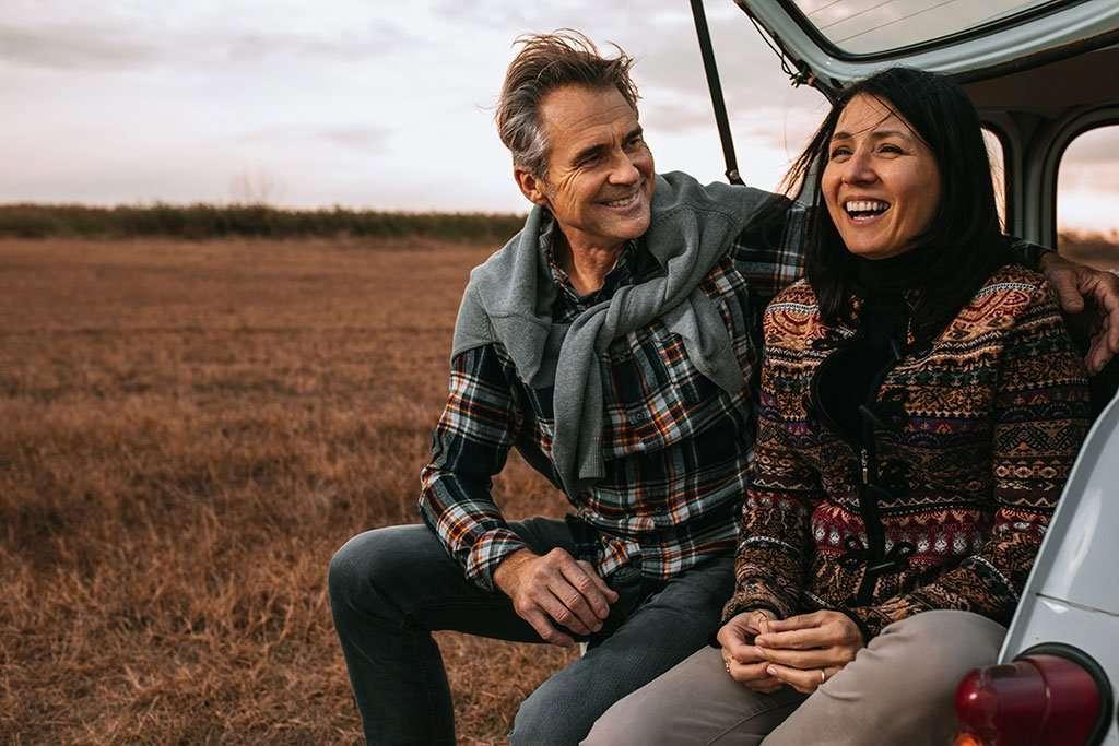 Man and woman sitting in the back of a car by a field.