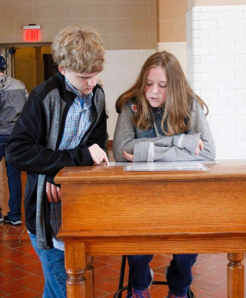 two kids homeschool and travel reading at Ellis Island
