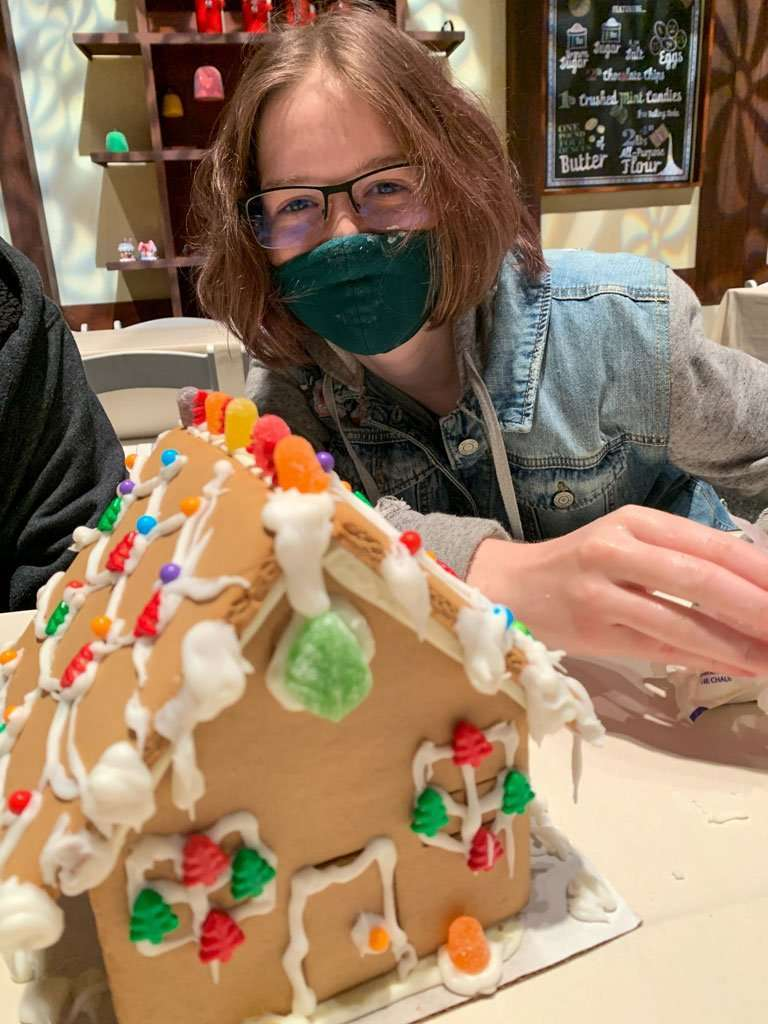 Girl with decorated gingerbread house