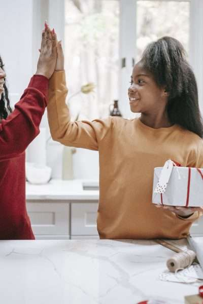 African american mother with happy daughter giving five in kitchen