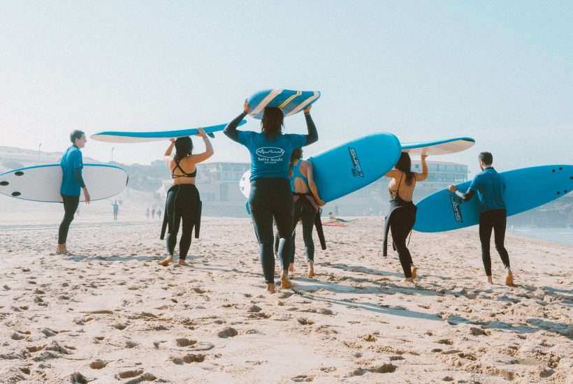 Group of people carrying surfboards