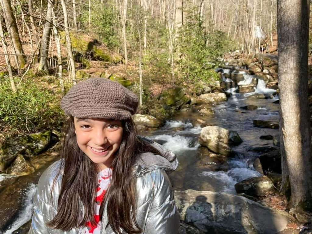 young girl in front of river at Anna Ruby Falls