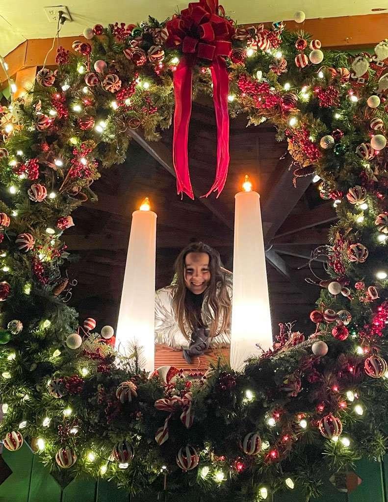 girl in lighted Christmas Wreath in Helen Georgia