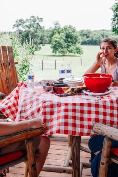 ranch, 3 people gathered around a red checked table eating a 4th of July picnic