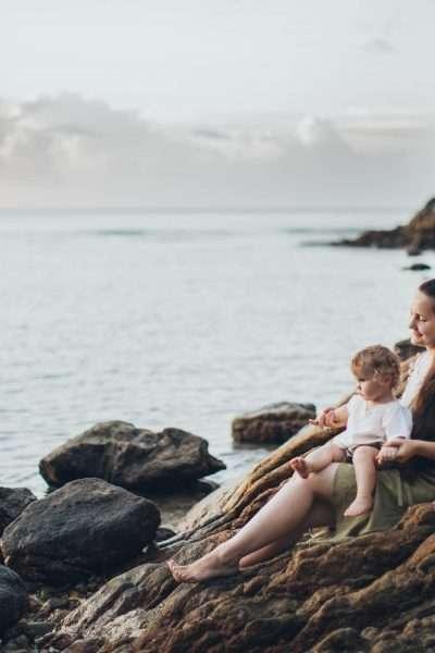 Man and woman sitting on rock near seashore