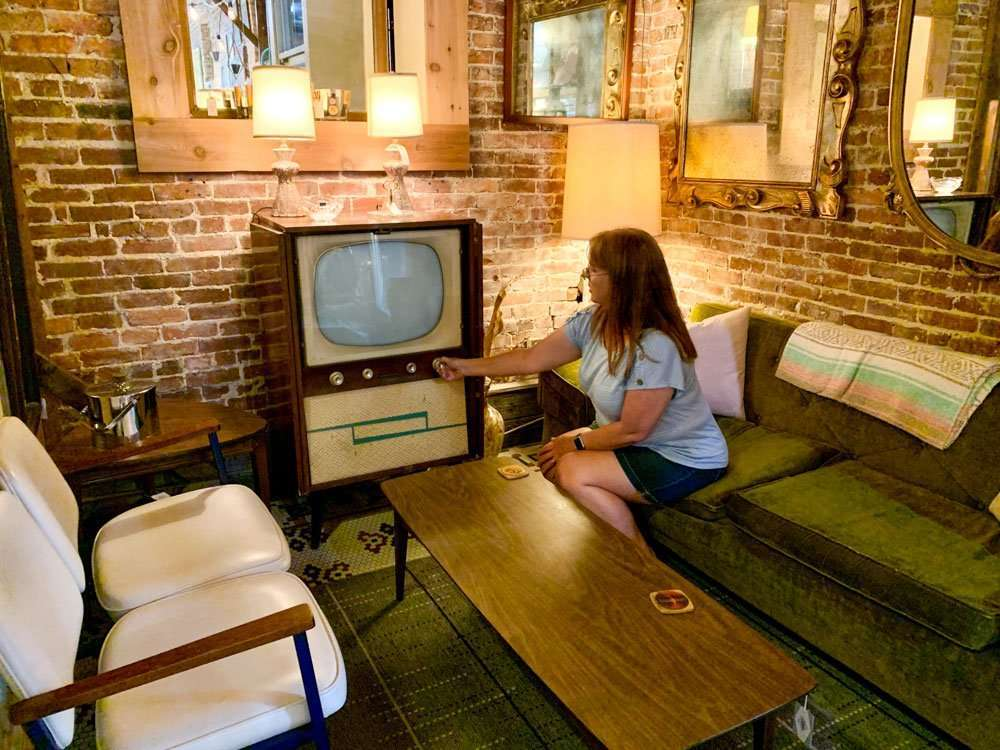 woman sitting on older couch with 1950s style television