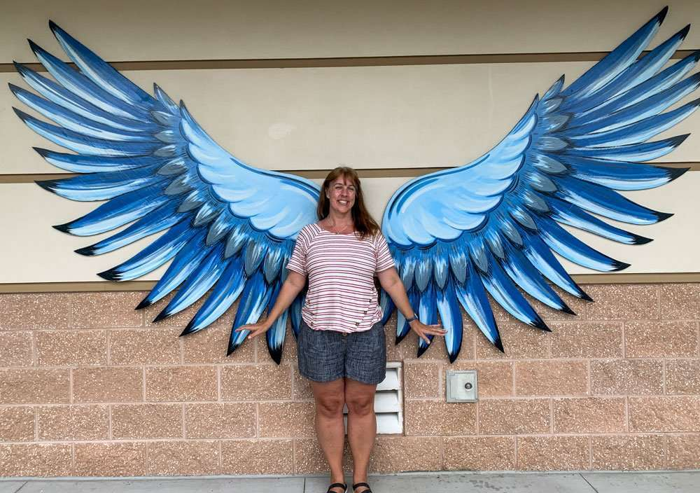 Wings of the West Scrub Jay Wings mural and woman.
