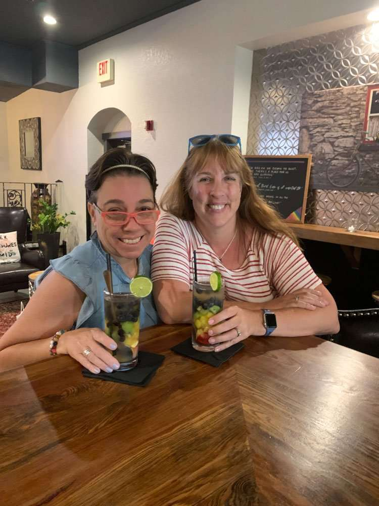2 woman drinking brightly colored fruity drinks.
